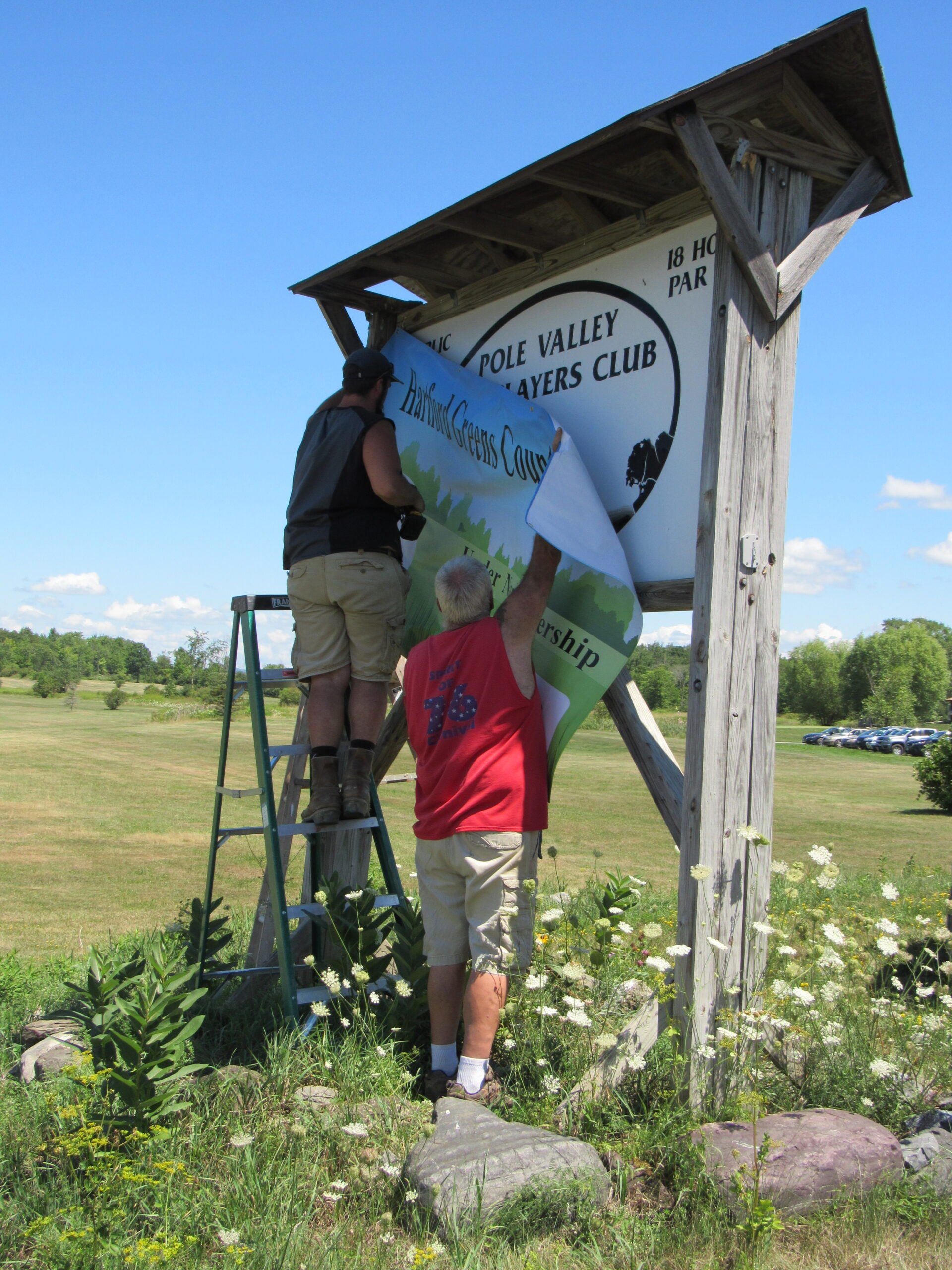 Employees hanging up new signage by road for Hartford Greens Country Club