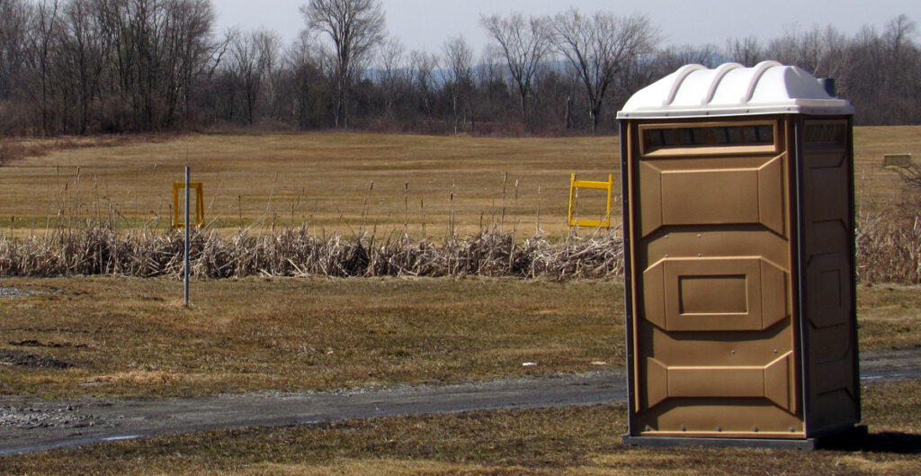 Course Under Construction- Porta-potty in parking lot for players use.